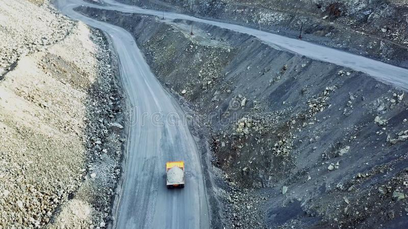 Dump truck is at quarry. Top view of driving orange dump truck with rubble on road open pit. Heavy transport in mining. Industry royalty free stock photo