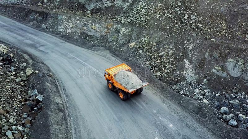 Dump truck is at quarry. Top view of driving orange dump truck with rubble on road open pit. Heavy transport in mining. Industry stock images