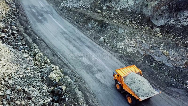 Dump truck is at quarry. Top view of driving orange dump truck with rubble on road open pit. Heavy transport in mining. Industry stock photo