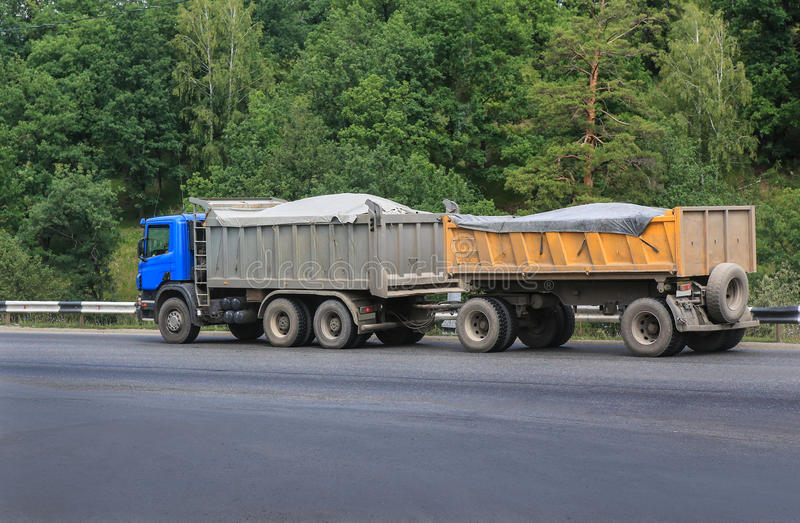 Dump truck with trailer. Moves on highway in country stock photography