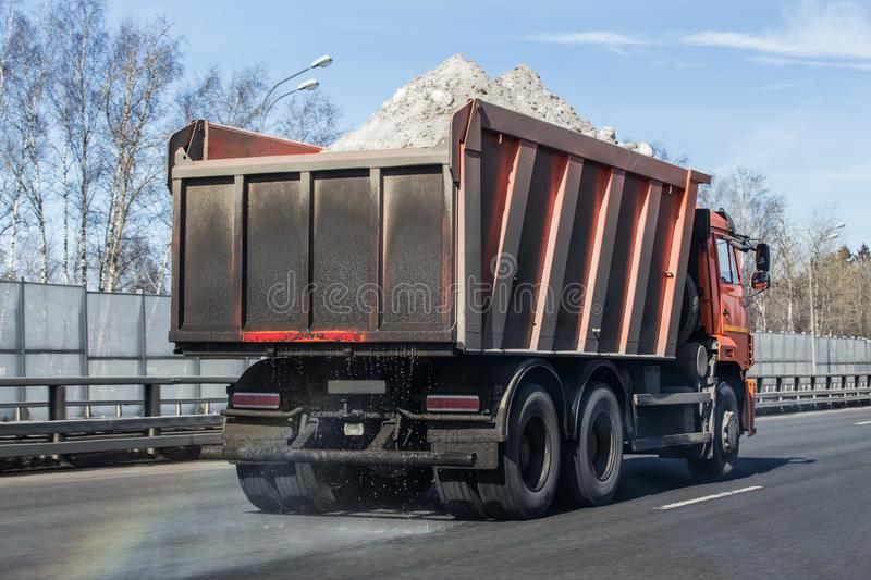 Dump truck transports snow on the highway. In the spring stock image