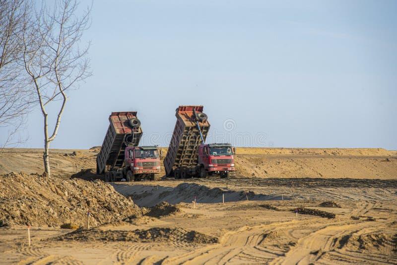 Dump truck unloading sand Two red dump trucks unload the soil stock image
