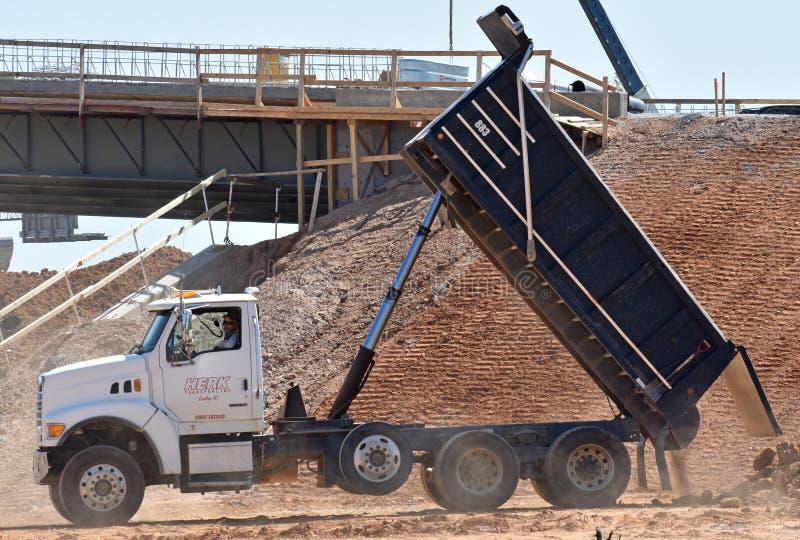A dump truck unloads dirt royalty free stock photography