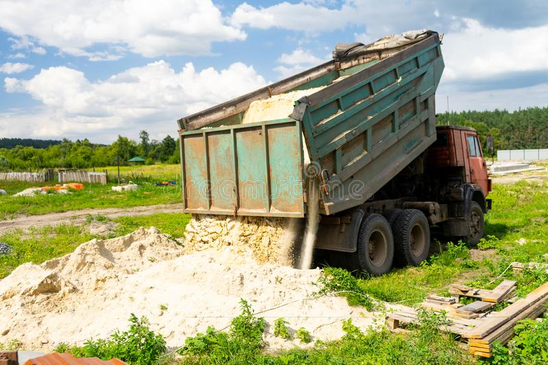 The dump truck unloads sand. The truck dumped the cargo. Sand and gravel. Construction site, materials warehouse. royalty free stock photography