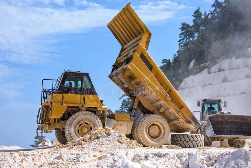 Dump truck working with excavator in Marble Quarry. Thassos, Greece stock image
