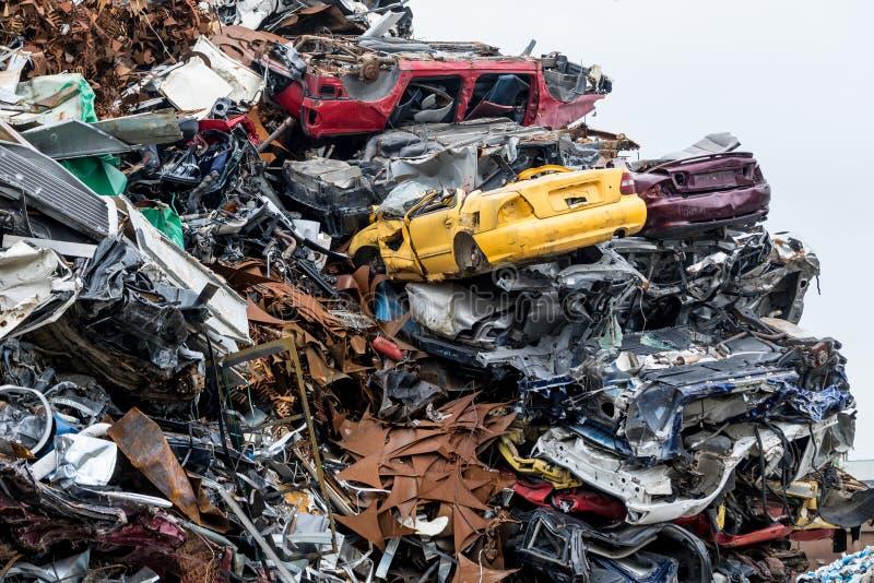 Dumpa jordning Hög för restmetall Komprimerade krossade bilar gås tillbaka för återanvändning Järnavfalls som malas i industriomr royaltyfri foto