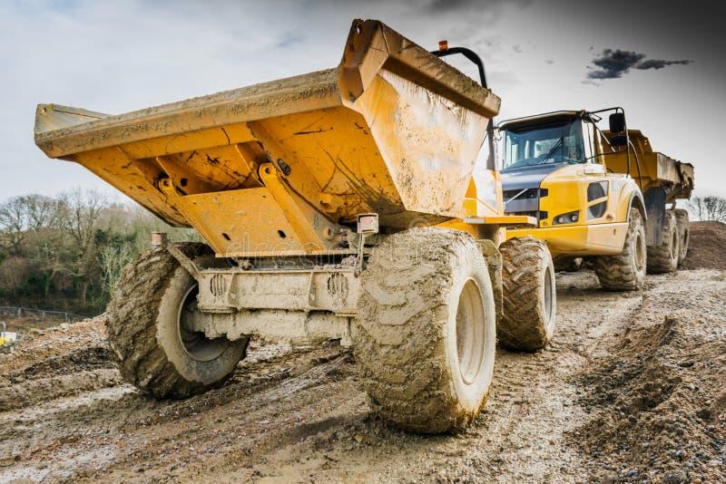 Dumper och lastbil i gyttja på konstruktionsplats arkivbilder