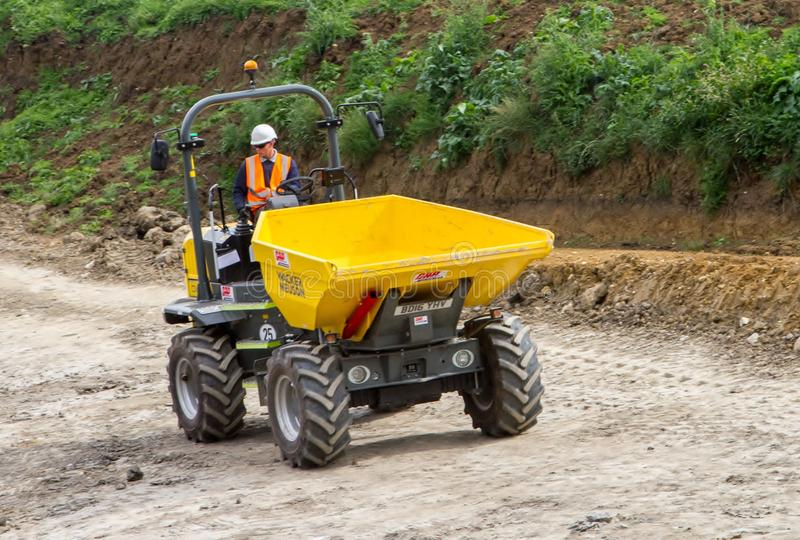 A dumper truck on a building site tipping soil. Large heavy machinery on a building site quarry moving earth excavating clearing rocks and earth stock photography