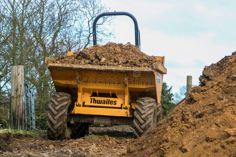 A dumper truck on a building site tipping soil. Large heavy machinery on a building site quarry moving earth excavating clearing rocks and earth royalty free stock photo