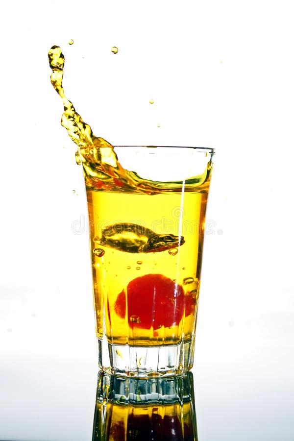 Dumping cherry and Spilling out water. Dumping cherry to little glass and Spilling out water royalty free stock image