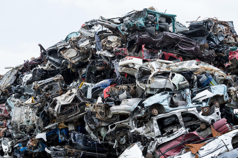 Dumping ground. Scrap metal heap. Compressed crushed cars is returned for recycling. Iron waste ground in the industrial area. Stacked automobile royalty free stock image
