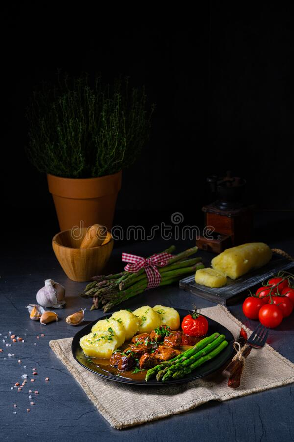 Dumplings with beef goulash and green asparagus royalty free stock photo