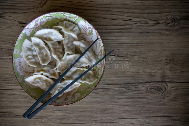 Dumplings in ceramic bowl on wooden table. Chinese cuisine dish top view photo. Dumpling banner template with text place. China restaurant. Dumpling with stock images