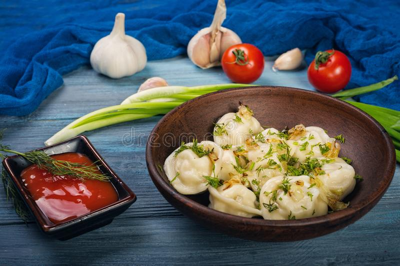 Dumplings in clay plate. On blue, wooden background stock image