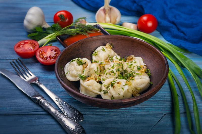 Dumplings in clay plate. On blue, wooden background royalty free stock image