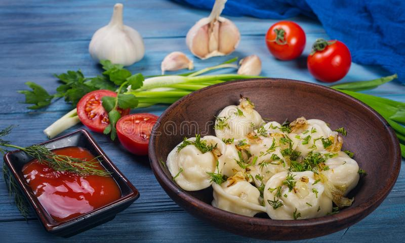 Dumplings in clay plate. On blue, wooden background royalty free stock photography