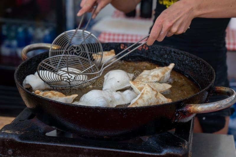 Dumplings fried in hot oil pan. Dumplings fried,Deep Frying in hot oil pan, street food during the day,italian traditional food royalty free stock images
