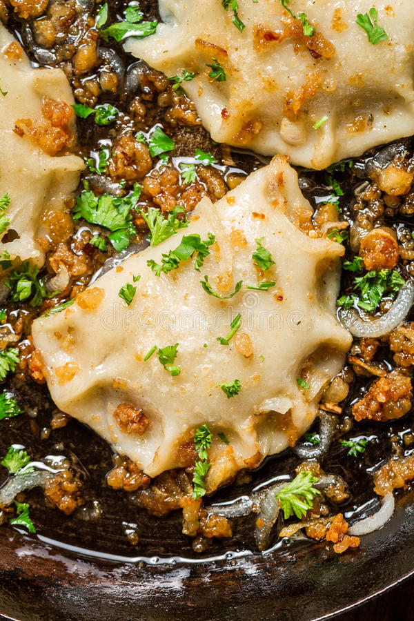 Dumplings with onion and parsley on pan stock photo