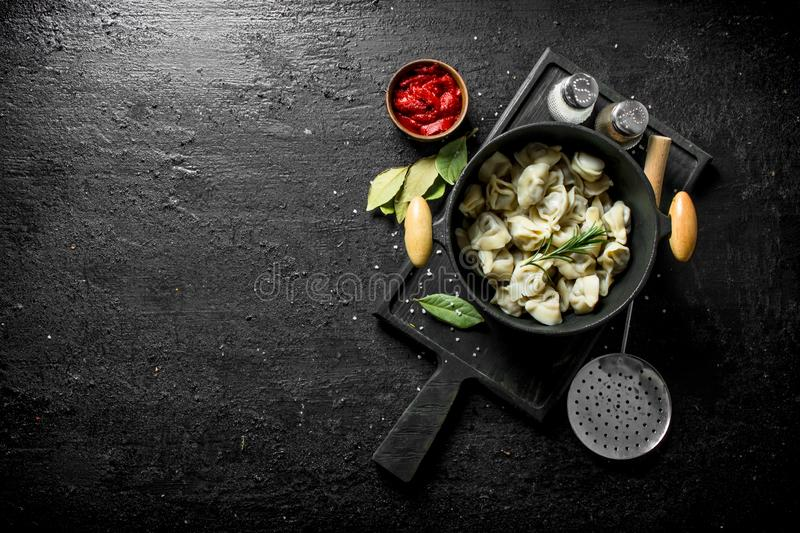 Dumplings in a pot with tomato paste, Bay leaf and spices. On black rustic background stock image