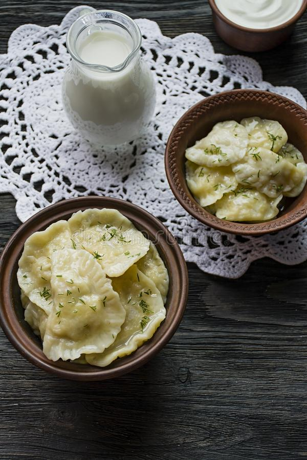 Dumplings with potatoes and cabbage. Sour cream, milk and greens. Traditional dish of Ukraine. Dark wooden background royalty free stock photo