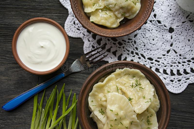 Dumplings with potatoes and cabbage. Sour cream, milk and greens. Traditional dish of Ukraine. Dark wooden background stock photos