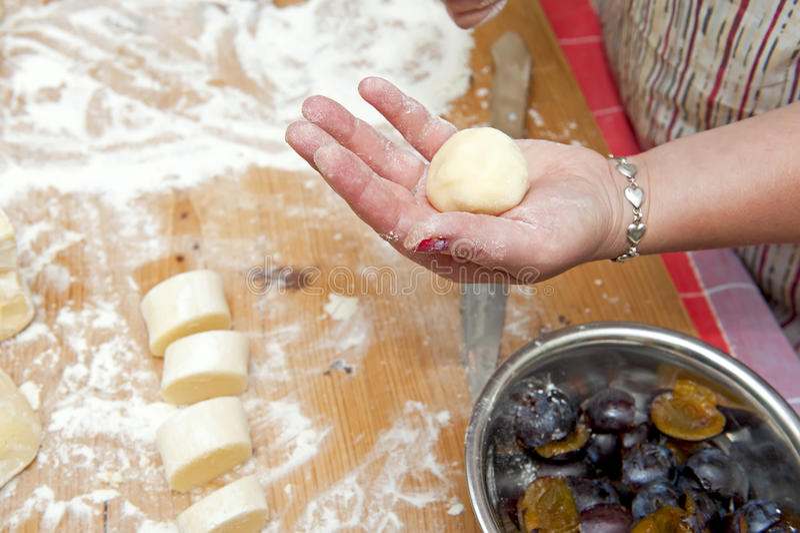 Dumplings stuffed with plum. Closeup view of a hand with ready dumpling stuffed with plum stock photography