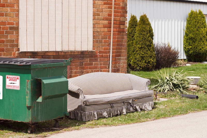 Dumpster couch. Old couch outside beside a trash dumpster stock photos