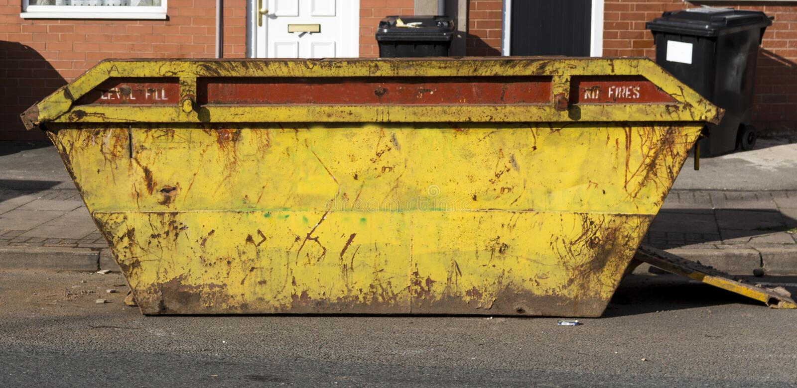 Dumpster. Large yellow dumpster or skip on the street stock image