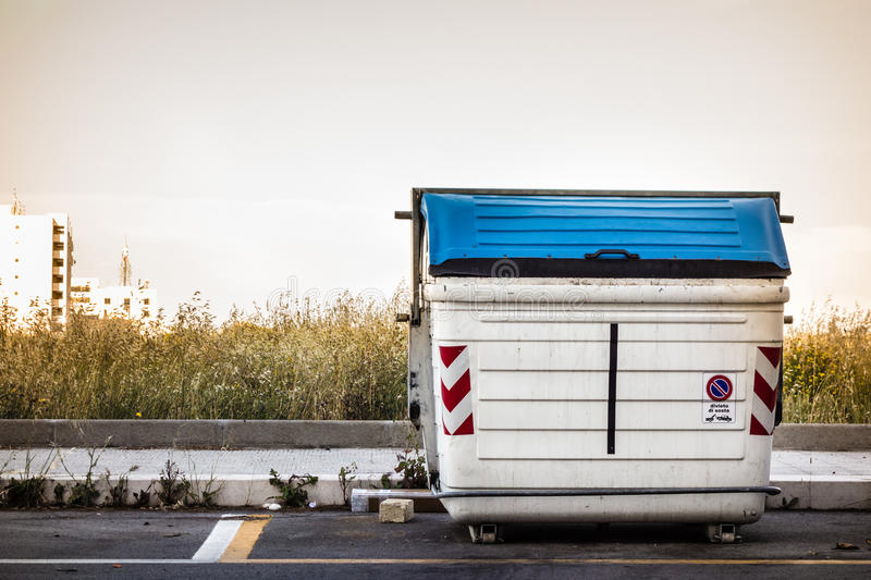 Dumpster. A white and weathered dumpster at the street side royalty free stock image