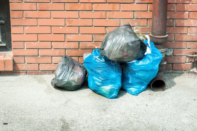 Dumpte het hoogtepunt van huisvuil plastic zakken van troep op de straat wachtend op dumpstervrachtwagen om hen te verzamelen stock afbeeldingen
