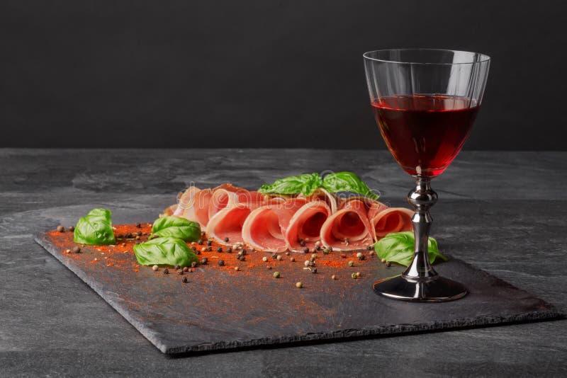 Dun gesneden balyk en een glas rode wijn op de verzadigde zwarte achtergrond Droge rode wijn, traditionele Italiaanse snacks, bas stock afbeelding