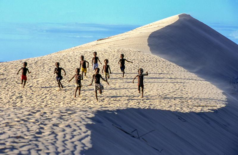 Duna con i ragazzi che corrono a Soalara sul Madagascar immagine stock