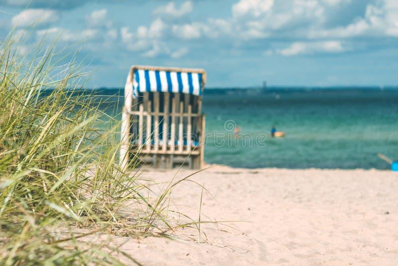 Duna con una certa erba e sedie di spiaggia di legno tradizionali sulla spiaggia sabbiosa La Germania del Nord, sulla costa di Ba immagine stock