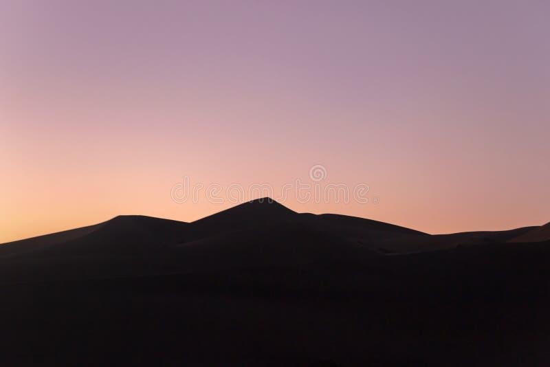 Duna de arena en cielo rojo en desierto en la puesta del sol fotos de archivo