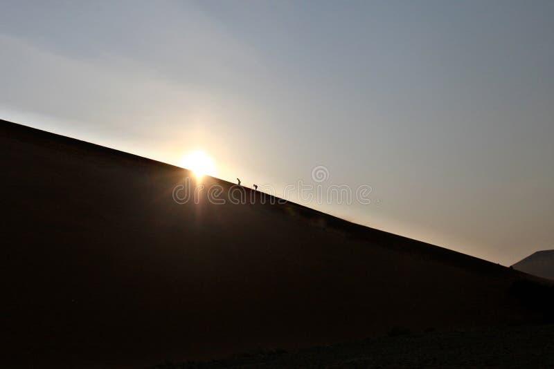 Duna di sabbia rampicante della gente in deserto fotografia stock libera da diritti