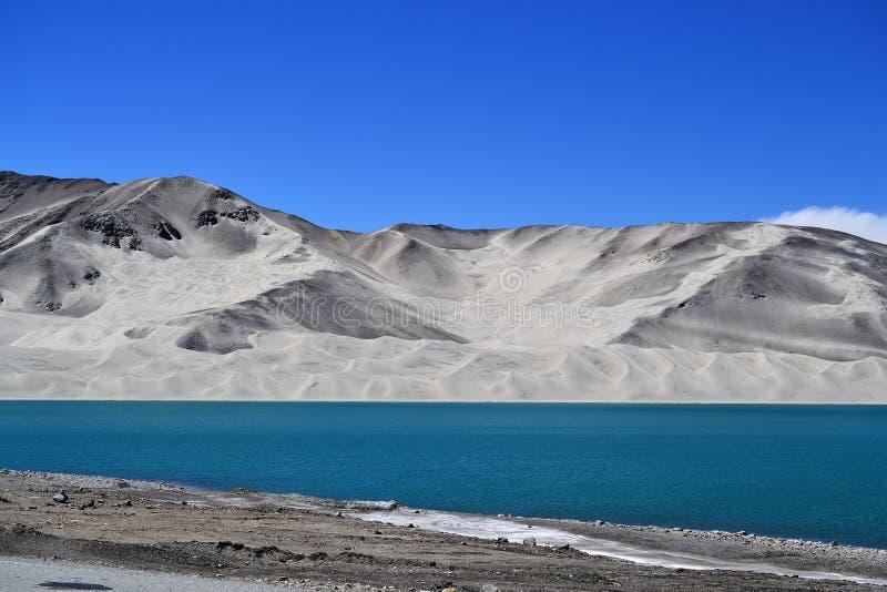 Dunas de areia e água azul de turquesa no lago Bulunkou na estrada de Karakoram, Xinjiang fotos de stock royalty free