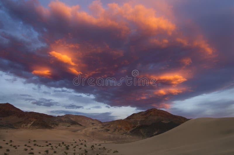 Dunas de areia e um por do sol impetuoso para criar uma paisagem dramática foto de stock royalty free