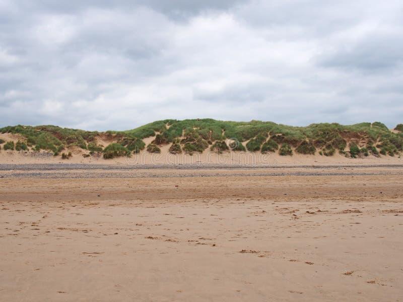 Dunas de areia gramíneas na borda de um Sandy Beach liso com pegadas na luz solar do verão com céu azul e nuvens imagem de stock royalty free