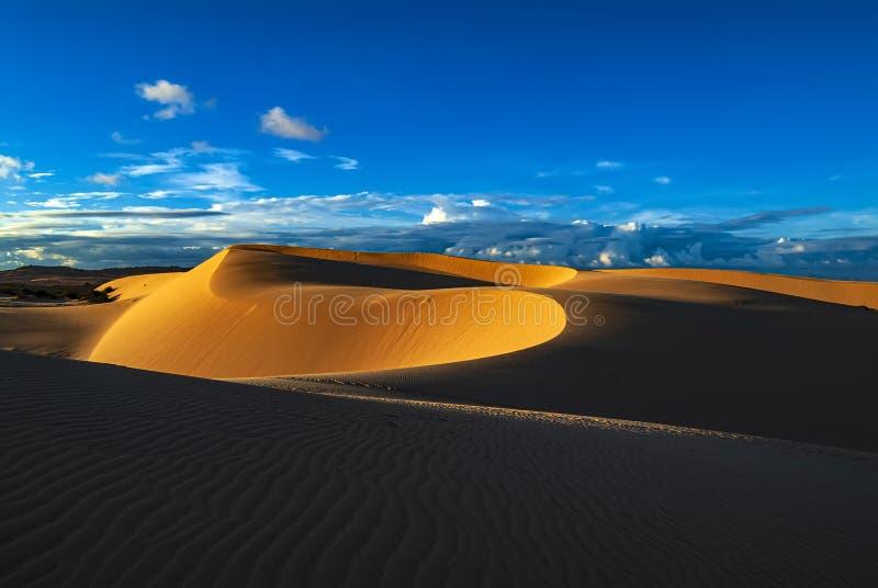 Dunas de arena en la puesta del sol con el cielo azul fotos de archivo libres de regalías