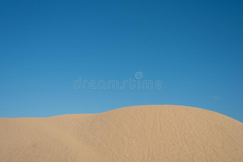 Dunas de arena hermosas contra fondo brillante del cielo azul imagenes de archivo