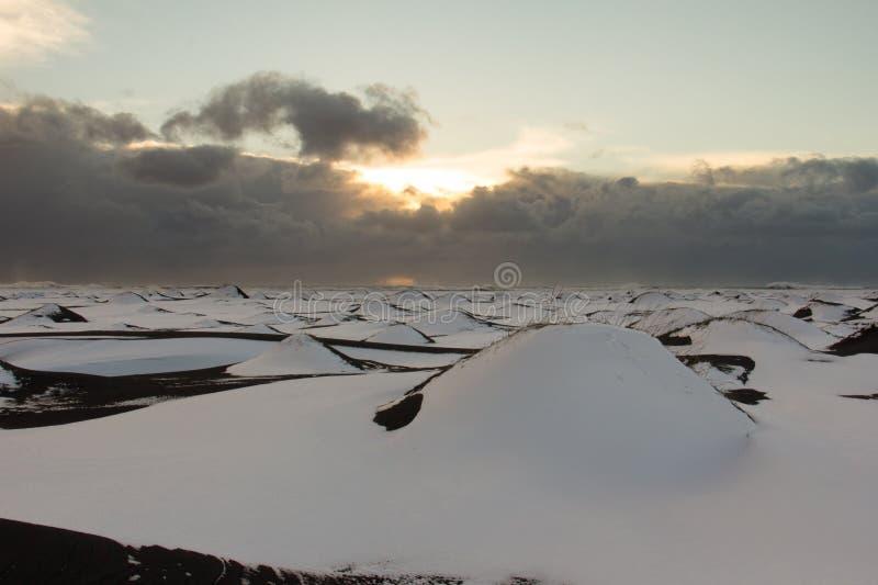 Dunas de arena negras nevadas debajo de los cielos tempestuosos foto de archivo