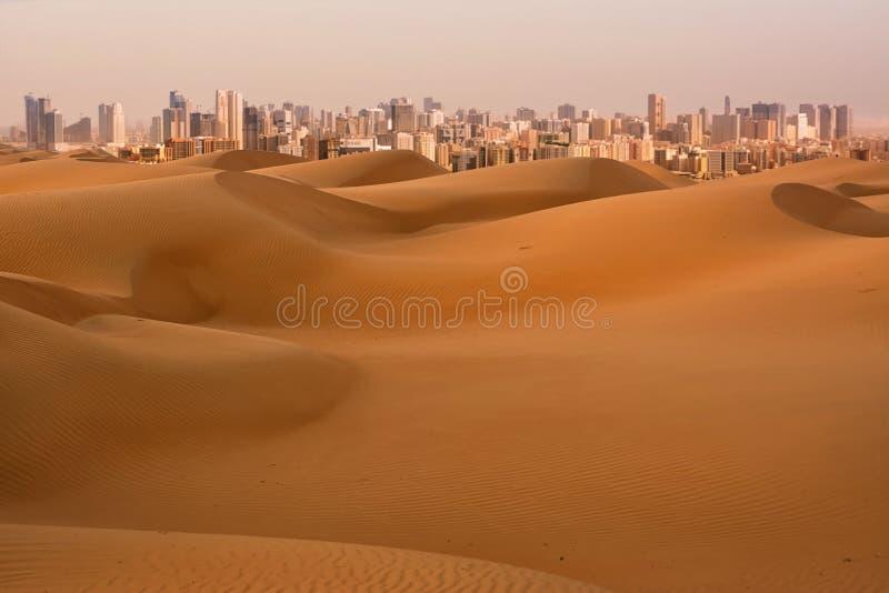 Dunas del desierto en el amanecer y de rascacielos de Dubai United Arab Emirates imagenes de archivo