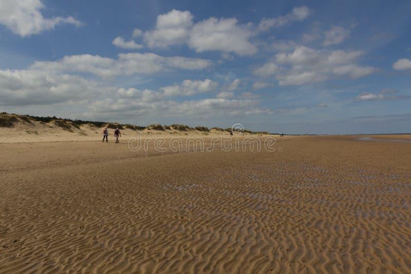 Dunas e povos de areia que andam na praia no Wells-seguinte--mar imagem de stock