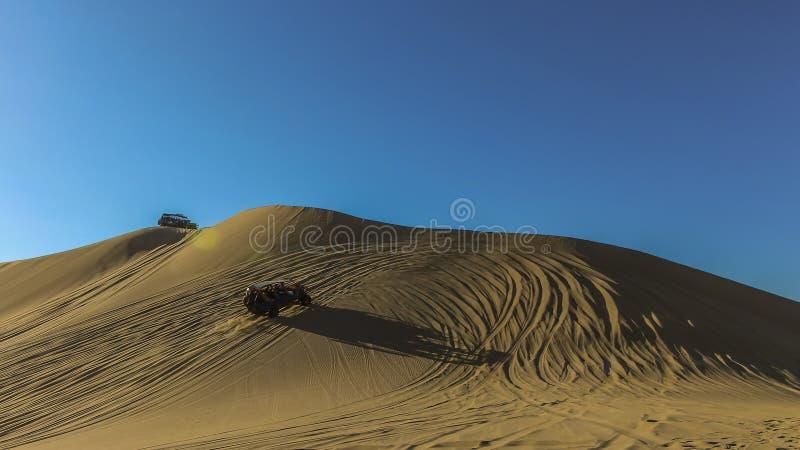 Dunas y cochecillos de arena contra el cielo azul en Huacachina, Per? imagen de archivo libre de regalías