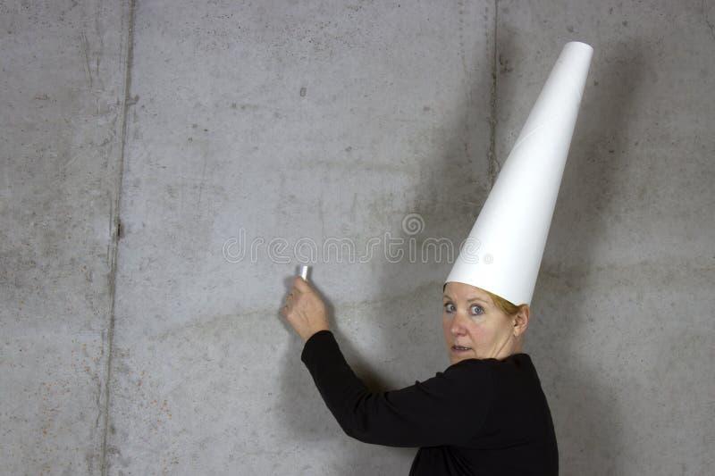 Dunce ΚΑΠ, γυναίκα, που γράφει στον τοίχο στοκ εικόνες