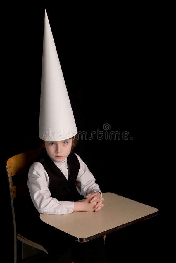 Dunce cap. Sad young boy in a dunce cap at his school desk over a black background stock photography