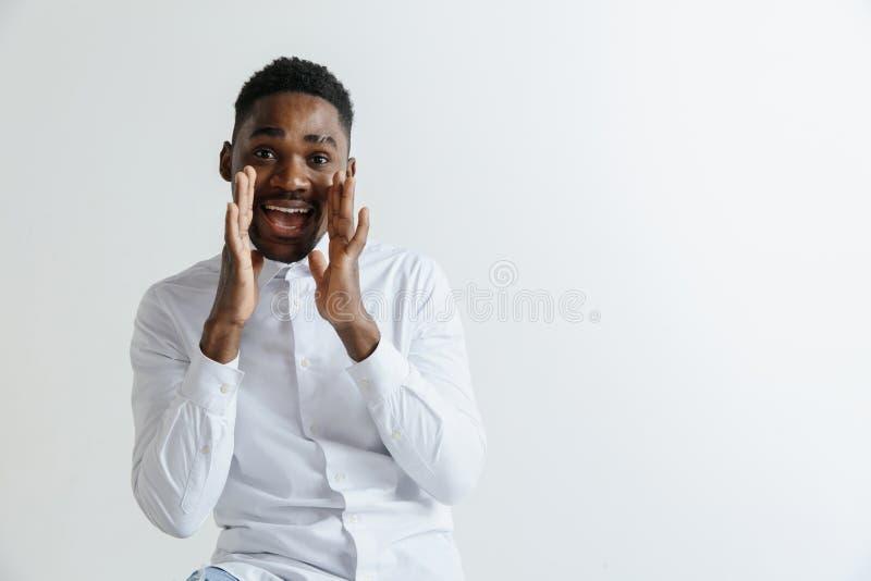dundersuccé Attraktiv manlig i halvfigur främre stående på grå studiobackgroud Emotionell förvånad skäggig man för ung afro arkivbild