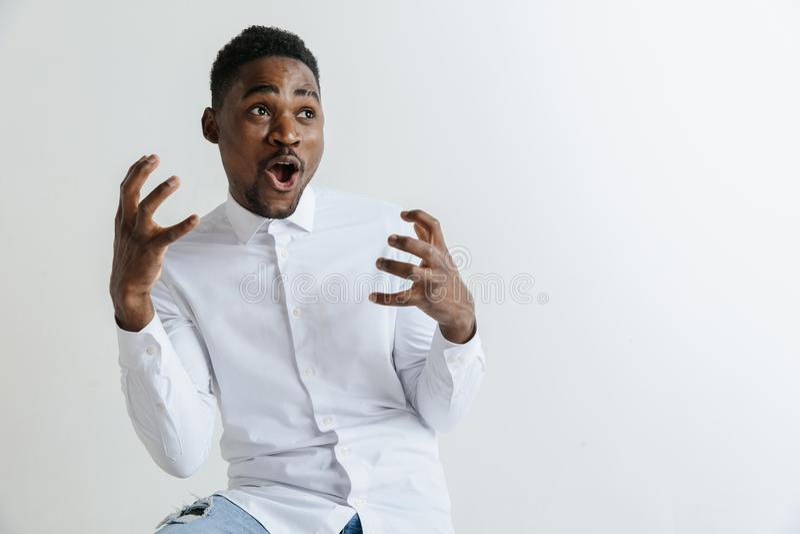 dundersuccé Attraktiv manlig i halvfigur främre stående på grå studiobackgroud Emotionell förvånad skäggig man för ung afro royaltyfri fotografi