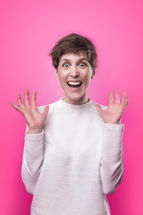 dundersuccé Härlig kvinnlig i halvfigur främre stående som isoleras på rosa studiobackgroud fotografering för bildbyråer