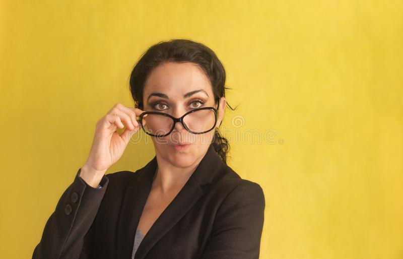 dundersuccé Härlig ung affärskvinna, med råttsvansen, exponeringsglas och det svarta omslaget som isoleras på en bakgrund Förvåna arkivfoton